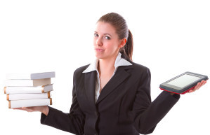 Photo of woman holding e-reader and books.